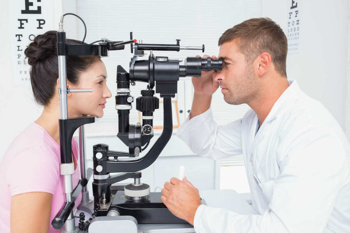Male optician examining womans eyes through slit lamp in clinic