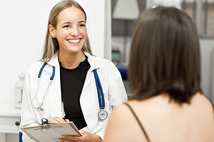 Female doctor explaining diagnosis to her patient. Brunette woman having consultation with smiling blonde girl in medical office.