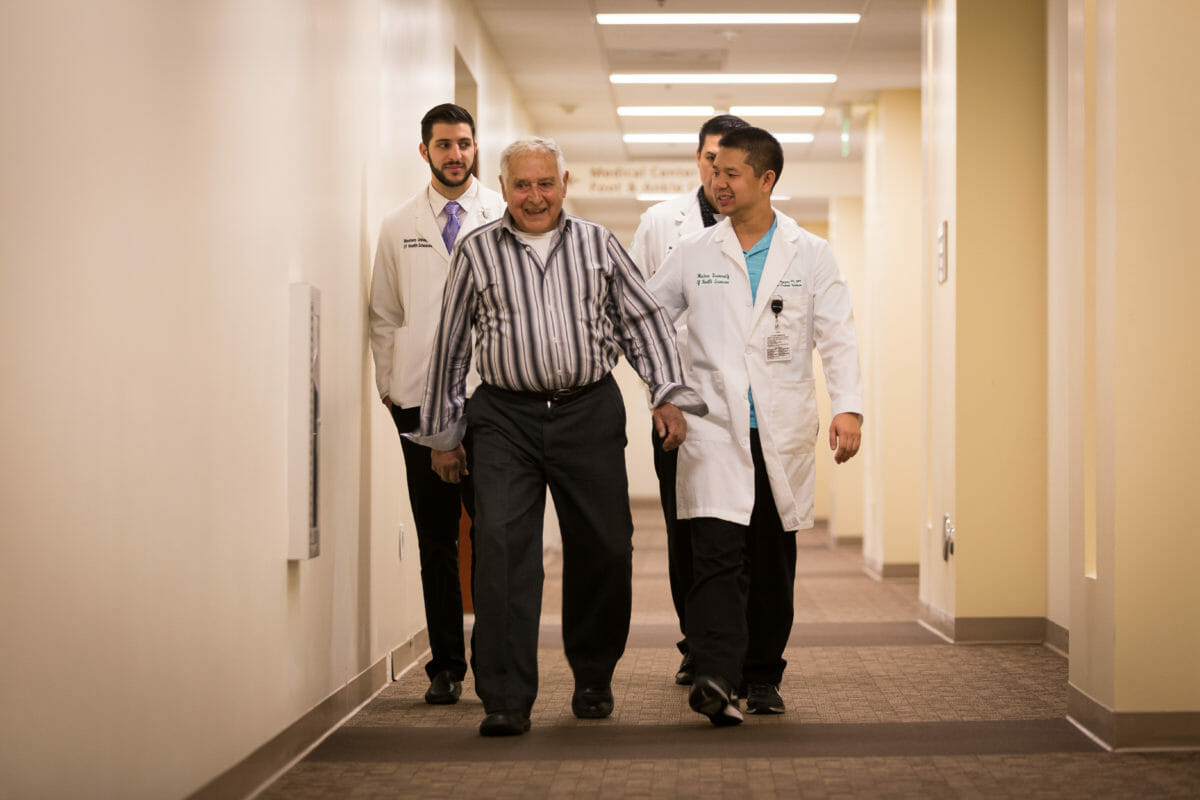 Doctors and patient walking down hall
